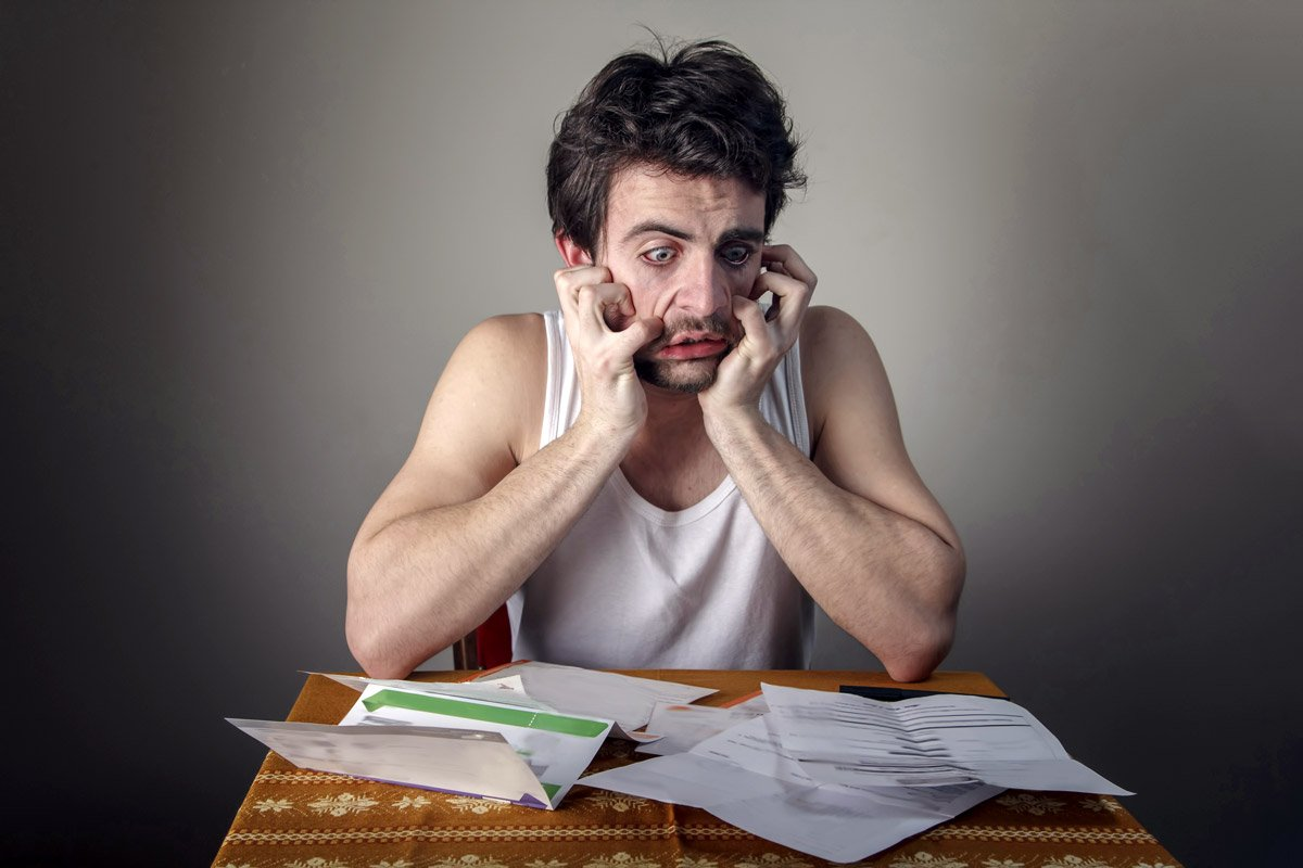 A man looks stressed out as he looks at his bills.