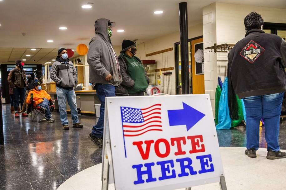 """People wait in line to cast their ballots in Minneapolis, Minnesota on November 3, 2020. - The United States started voting Tuesday in an election amounting to a referendum on Donald Trump's uniquely brash and bruising presidency, which Democratic opponent and frontrunner Joe Biden urged Americans to end to restore """"our democracy."""" (Photo by Kerem Yucel / AFP) (Photo by KEREM YUCEL/AFP via Getty Images)"""