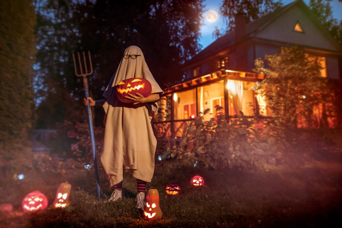 A man dresses as a ghost with a pitchfork and carved pumpkins all around him.