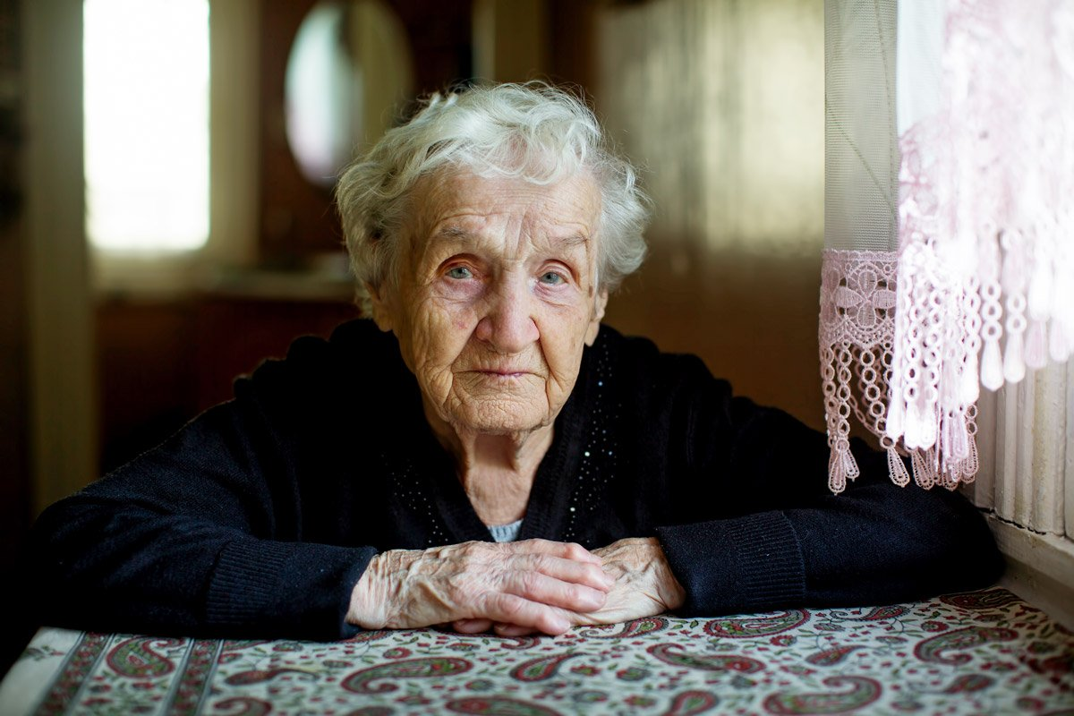 An elderly woman sits at her kitchen table.