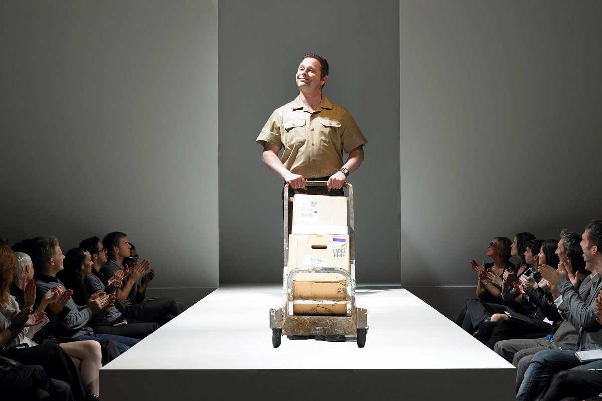 A delivery person stands on a catwalk with boxes to deliver.