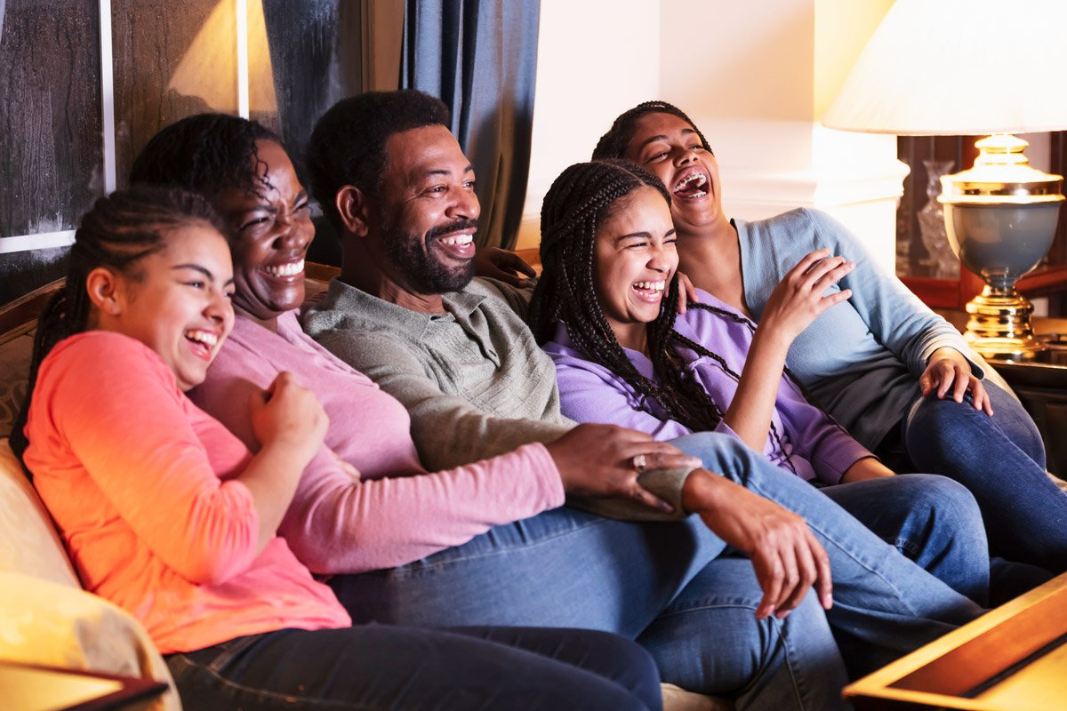 A family watch television together on their couch.
