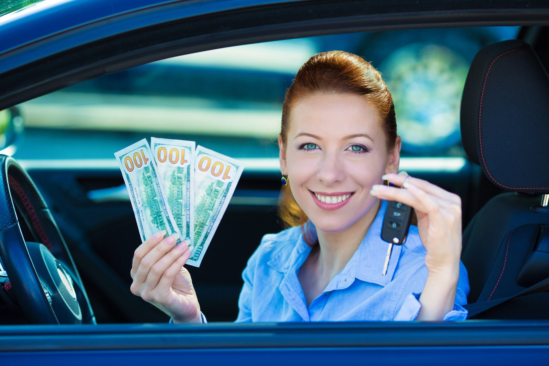 Woman in a car holding up money