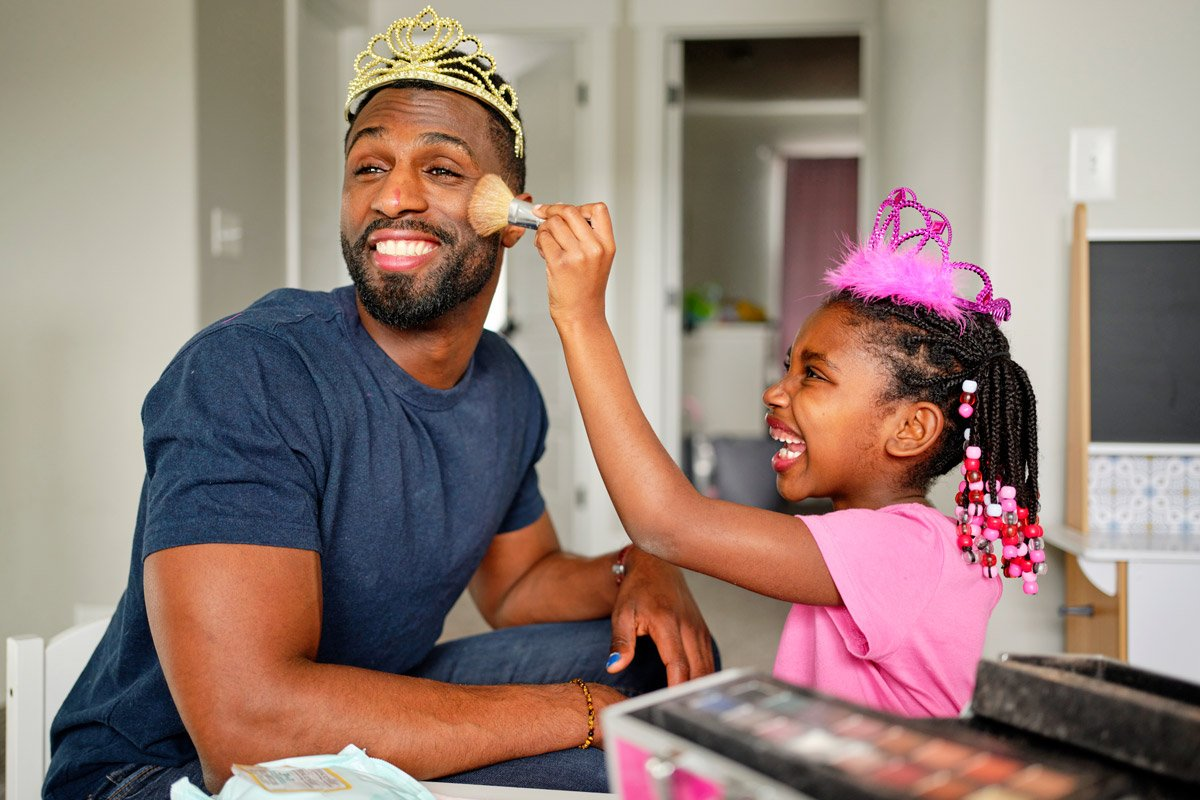 A father lets his daughter put make up on him.